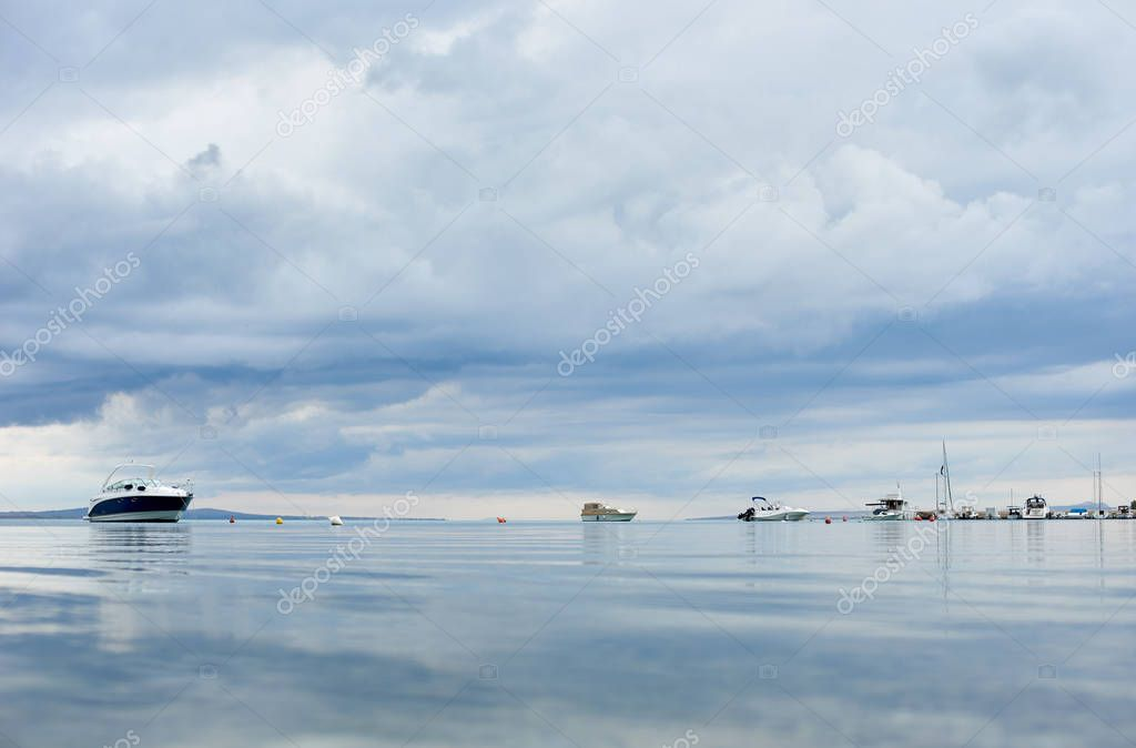 Beautiful seascape on summer cloudy day. Luxurious white anchored motorboats and yachts, cloudy sky reflecting in crystal clear glistering lagoon water