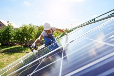 Worker mounting solar panels for renewable energy on house's roof. Using special equipment, wearing protective helmet. Environment friendly,resources saving, using renewable solar electricity.