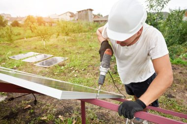 Close-up angled view of technician working with screwdriver connecting solar photo voltaic panel to exterior metal platform. Alternative renewable ecological green sun energy sources concept.