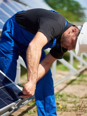 Technician working on exterior voltaic stand-alone solar panel system installation on bright sunny summer day. Renewable ecological cheap green energy production concept.