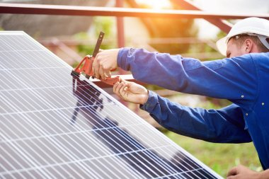 Process of connecting solar photo voltaic panel by professional technicians outdoors on bright sunny summer day. Stand-alone exterior solar panel system installation concept.