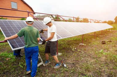 Team of workers finish assembling exterior stand-alone solar photo voltaic panel system in green field in front of rural cottage on sunny summer day. Alternative renewable ecological green energy.