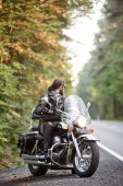Fotografie Bearded biker in black leather clothing sitting on cruiser motorcycle on country roadside on background of empty straight asphalt road and green trees bokeh foliage.