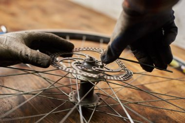 close up of mechanic working in bicycle repair shop fixing bike wheel using special tool