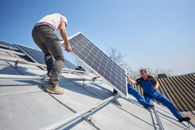 Electricians lifting blue solar module on roof of modern house