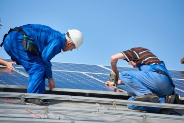 Electricians mounting blue solar module on roof of modern house. Alternative renewable energy ecological concept.