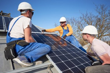 Three electricians mounting blue solar module on roof of modern house