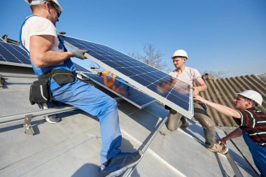 Electricians lifting blue solar module on roof of modern house. Alternative renewable energy ecological concept.