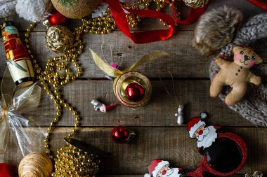 Handmade Christmas toys and decorations, warm woolen hat on wooden rustic background.