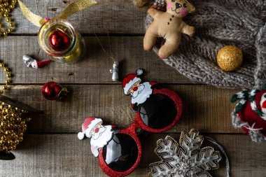 Handmade Christmas toys and decorations, funny Santa glasses, warm woolen hat on wooden rustic background.