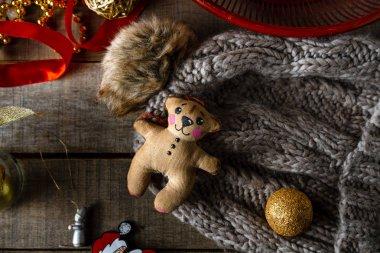 Handmade Teddy bear Christmas toy, warm woolen hat on wooden rustic background.