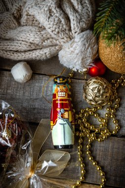 Christmas wooden toy Nutcracker, decorations, warm woolen hat on wooden rustic background.
