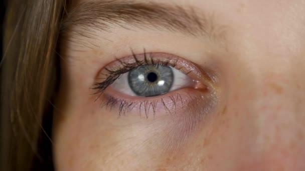 vereinzelt blaues Auge einer jungen schönen Frau im schwarzen Studio