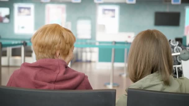 Two happy caucasian woman talking in airport and waitng for flight