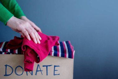 Donation Concept. Woman Droping her Used Old Clothes into a Donate Box