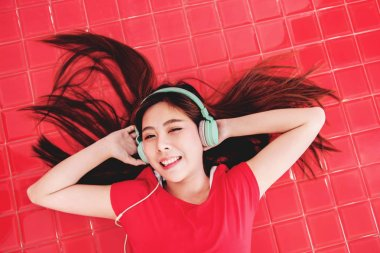 Happy Young Woman Lay on the Red Floor to Listening Music via Headphone in the Room. Smiling and Looking at Camera, Top View