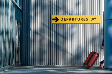 Transportation and Vacation Concept, Traveler Walking with Suitcase and Follow the Departures Sign in the Airport