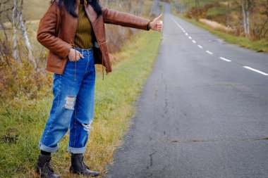 Travel and Freedom Concept. Young Hitchhiker Traveler Woman standing on the Roadside