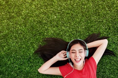 Happy Young Woman Lay on Green Grass to Listening Music via Headphones in the Park. Smiling and Closed Eyes, Top View