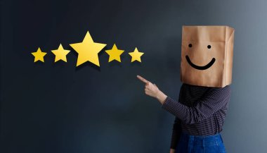 Customer Experience Concept. Woman Covered her head by Paper Bag with Happy Feeling Face and Pointing Hand to Five Star Services Rating Satisfaction. Client's Feedback and Online Review