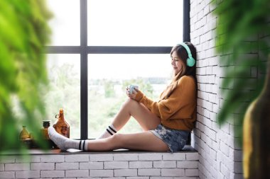 Young Woman Relaxing with Music From Headphone in Cozy House Nearby Window, Enjoying with Morning Sunshine and Hot Coffee