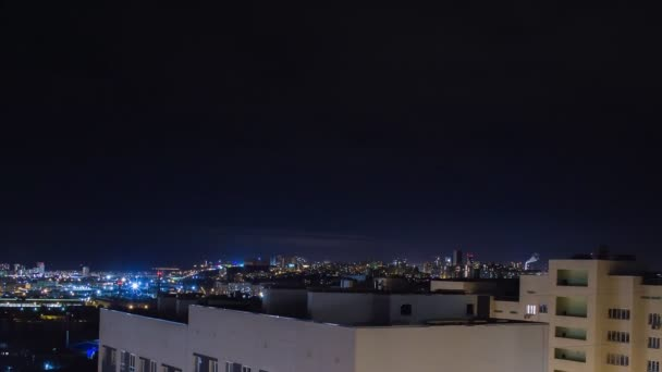 Night city skyline timelapse. Top aerial panoramic view of modern city from tower rooftop. Lights flicker in windows.