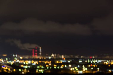 City skyline at night.Night view of a neighbourhood with low-rise apartment blocks illuminated window lights.Pipes of thermal power plant smoke.Blurry abstract image of industrial zone