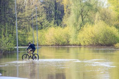 Bycyclist try to ride a bike during a flood at springtime. asphalt road under water as river was rising