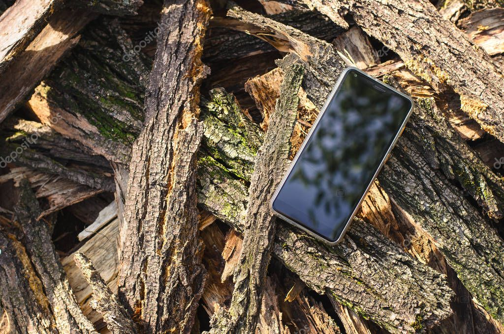 mobile phone black color is located in the open air on a pile of bark from acacia trees