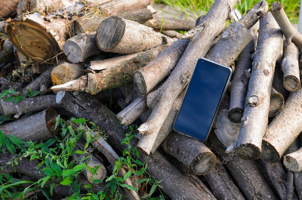 mobile phone black color is located on a pile of cut branches in the open air