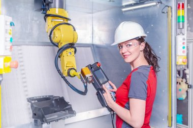 Young female technician while machine constructing in manufacturing plant