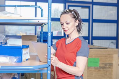 Young female warehouse worker in manufacturing plant