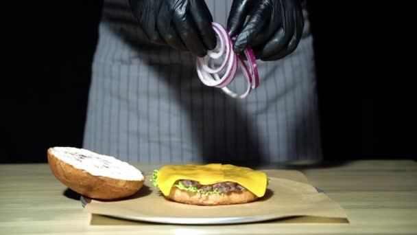 Chef készül a burger. Közeli kezét az ember dobott gyűrű hagyma egy hamburger. Lassított mozgás