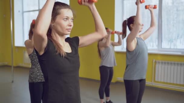 Skupina mladých žen, které cvičí s činkami ve fitness klubu. Zdravý životní styl koncept.