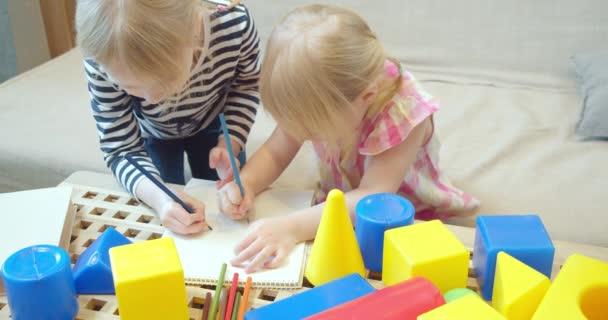 Dvě roztomilé děti dívky kreslí s barevnými tužkami na papíře doma. Dětský volný čas, kreativita a hry