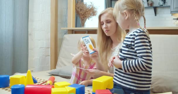 Young mother showing two daughters cards with letters and pictures studying the English alphabet while sitting on the sofa at home. Preschool education.