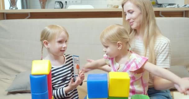 Cute girl showing cards with letters and pictures to little sister and mom. Learning the alphabet during the game. Preschool education.