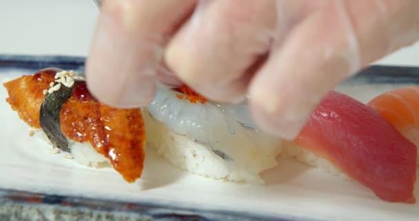 Friss sashimi egy tányéron. Férfi szakács kezek üzembe összetevők. A sushi készítésének folyamata.