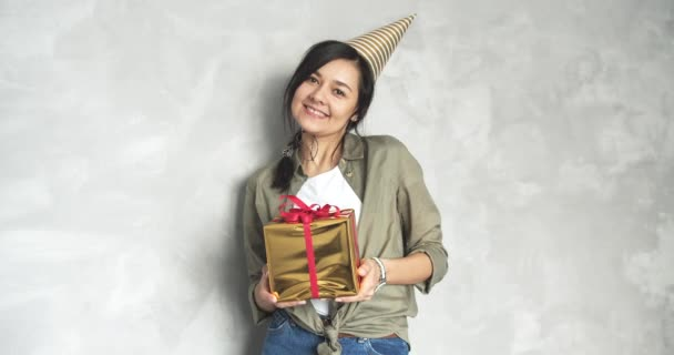 Portrait of a happy young woman in a birthday cap looking at the camera and giving a gift box against a gray background.