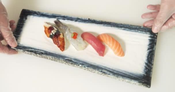 Detailní záběr lahodných sashimi s rýží, rybami a krevetami na talíři. Kuchaři servírují sushi rolky.