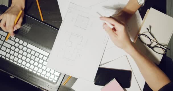 Zblízka pracoviště inženýrů nebo designérů diskutujících o projektových výkresech a pracujících na notebooku.