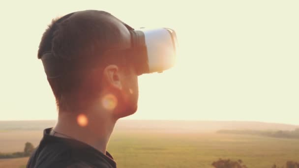 Young man uses virtual reality glasses in nature in a beautiful sunset