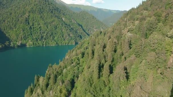 Hegyi tó türkizkék vízzel és zöld fa. Gyönyörű nyári táj hegyekkel, erdővel és tóval. Aerial 4k nézet. Drone lövés egy gyönyörű hegyi erdei tó