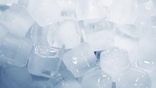 Makroaufnahme von Eiswürfeln aus klarem Wasser, die in Zeitlupe auf weißem Hintergrund schmelzen. Konzept: reines Bergquellwasser, Eis, Cocktails, frische und tiefgefrorene Lebensmittel.
