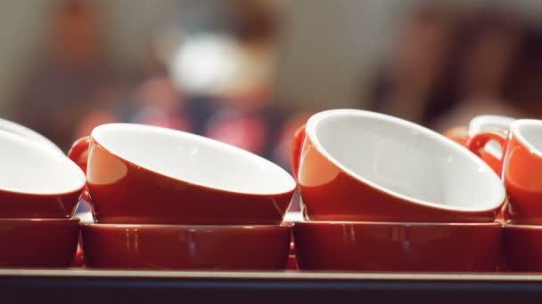 Prázdné červené šálky pro espresso a na kávu a mléko stojí a zahřívání na povrchu kávovar