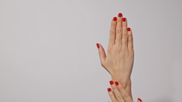 Szép fiatal Womans kezek élénk piros manikűr, egyrészt finoman masszírozni a másik, elszigetelt szürke háttér