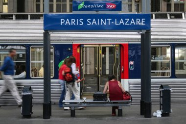 PARIS, FRANCE - AUGUST 10, 2006: Passengers rushing near a suburban train on a platform of Gare Saint Lazare train station. This station is one of the main railway hubs in Europe