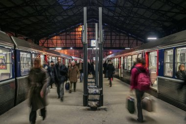 PARIS, FRANCE - DECEMBER 24, 2007: Passengers rushing near a suburban train on a platform of Gare Saint Lazare train station. This station is one of the main railway hubs in Europe