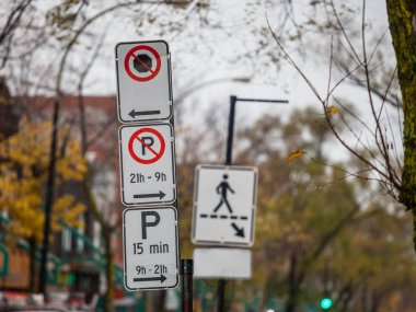 Typical North American paking and no parking signs with detailed instructions on the parking regulations taken in Montreal, Quebec, Canada, with a sign indicating pedestrian crossing in background