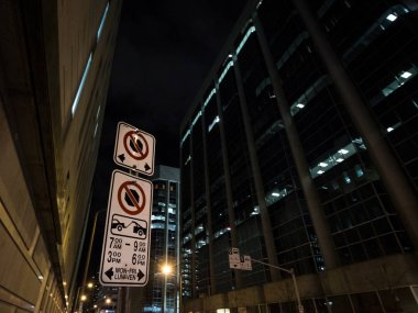 Typical North American paking and no parking signs with detailed instructions on the parking regulations taken at night in Ottawa CBD, Ontario, Canada, with a sign indicating bus lanes behind